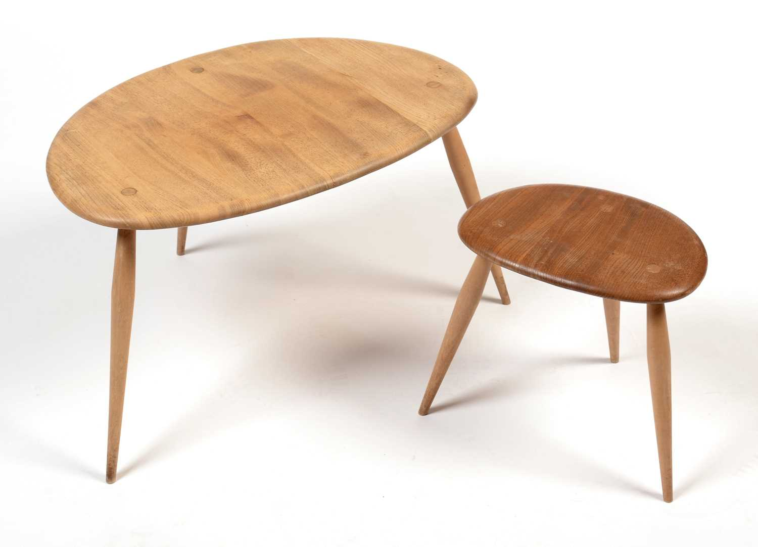 Ercol: two from a set of three beech and elm 'Pebble' tables.