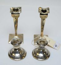 Two pairs of antique silver candlesticks.