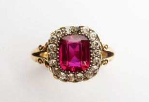A yellow metal, diamond, and synthetic ruby ring.