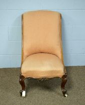A late Victorian walnut slipper chair, upholstered in peach fabric.