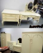 Ornate French-style cream and gilt-painted bedroom furniture.