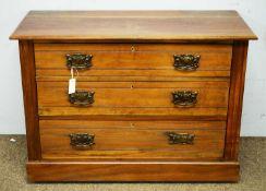 An Edwardian walnut three drawer chest.
