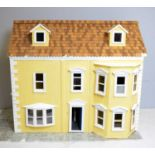 A doll's house incorporating a shop to one side.