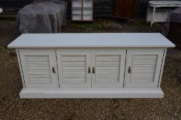 A large white painted sideboard with louvre panelled doors