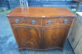 A mahogany crossbanded serpentine front cabinet