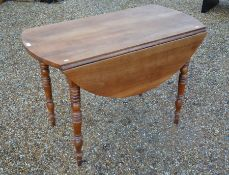 A 19th century fruitwood drop leaf table on turned supports