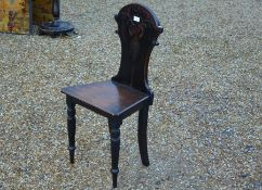 An antique carved mahogany hall chair