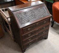 A profusely carved mahogany fall front bureau