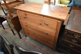 A modern stained pine chest of three long drawers