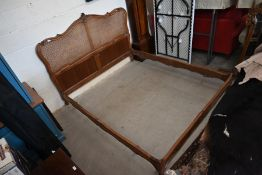 A French Louis XV style carved walnut and cane work panelled double bed frame