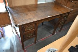 A panelled oak kneehole desk with five drawers