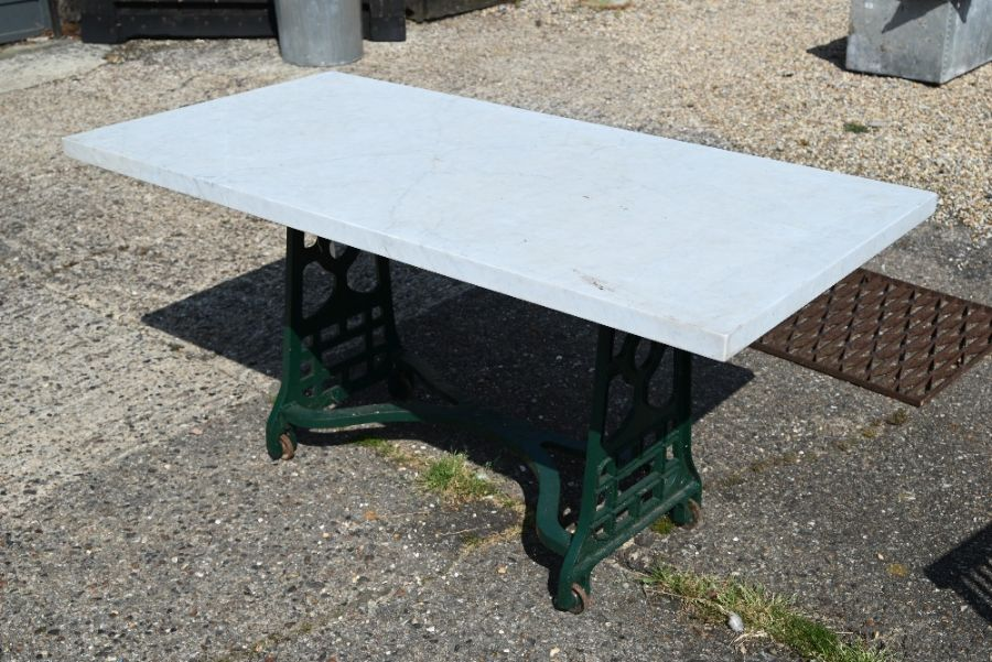 A solid marble top garden table on green painted cast iron base