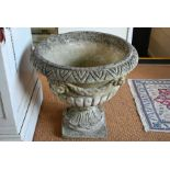 A large weathered cast stone garden urn