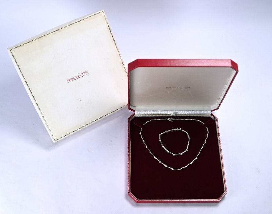 A white metal diamond set matching necklace and bracelet