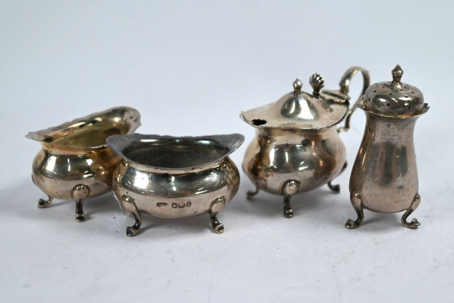 Silver cream jug and various condiments