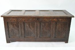 A late 17th/18th century carved oak coffer, on stile feet