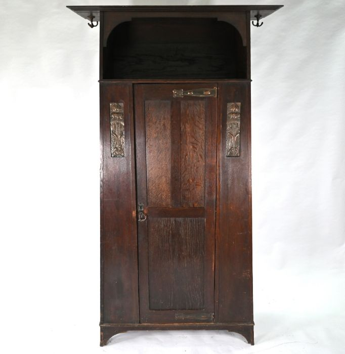 An Art & Crafts oak hall cupboard in the manner of Liberty & Co