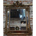 An antique gilt framed cushion mirror