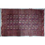 An old Turkoman rug with three rows of guls on red ground