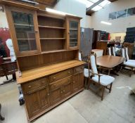 An Ercol dining suite comprising an extending dining table,
