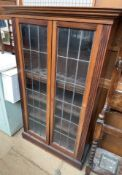 A 20th century mahogany bookcase together with two sewing tables and an Edwardian mahogany