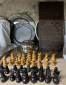 A turned chess set together with three pewter chargers,