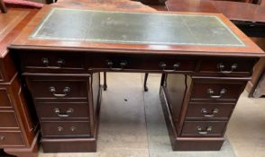 A reproduction mahogany pedestal desk with a green leather inset writing surface a central drawer