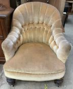 A Victorian upholstered button back elbow chair on turned legs
