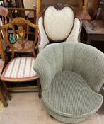An Edwardian mahogany elbow chair with an upholstered shield shaped upholstered back,