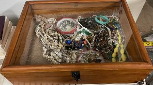 A table top display cabinet containing assorted costume jewellery including necklaces,