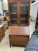 A 20th century oak bureau bookcase the moulded cornice above a pair of leaded glazed doors,