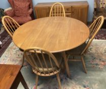 An Ercol drop leaf dining table together with four stick back dining chairs and a sideboard