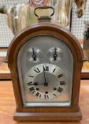 A 20th century oak cased bracket clock, with a domed top and carrying handle,