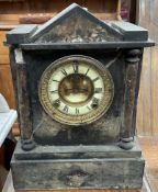A black slate mantle clock of architectural form