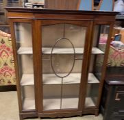 An Edwardian mahogany display cabinet with a breakfront top above a glazed door,
