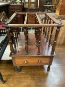 A Victorian mahogany Canterbury with three divisions above a base drawer on turned legs and casters