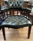 A green leather button back upholstered captain's chair