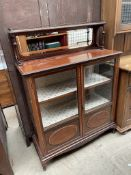 An Edwardian mahogany display cabinet, with a three quarter gallery and shelf above a mirror,