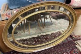 A 19th century gilt gesso wall mirror of oval form with a gadrooned rim and reeded inner oval