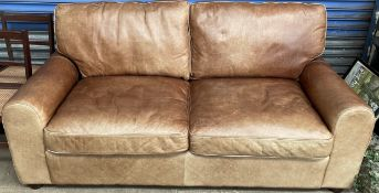 A brown leather two seater settee