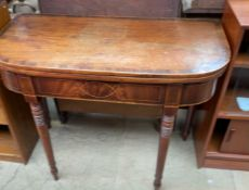 A Victorian mahogany tea table with an crossbanded D shaped top on turned legs