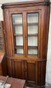 A 19th century mahogany standing corner cupboard with a pair of glazed doors to the top and