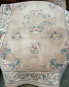 A Chinese pink ground rug together with another similar