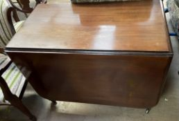 A Victorian mahogany gateleg dining table with a rectangular top and drop flaps on turned legs and
