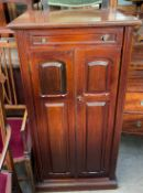 An Edwardian mahogany music cabinet with a rectangular moulded top above a rotating top drawer and