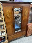 An Edwardian mahogany wardrobe with a central mirror and a base drawer on bracket feet together