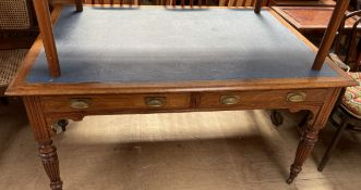 A Victorian oak library table with an inset top above drawers on reeded tapering legs and casters