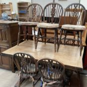 A 20th century oak drawleaf dining table with cup and cover legs together with a matched set of