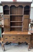 An oak dresser, the rack with a moulded cornice above shelves and cupboards,