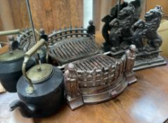 A pair of cast iron rampant lion door stops together with a fire grate and a kettle